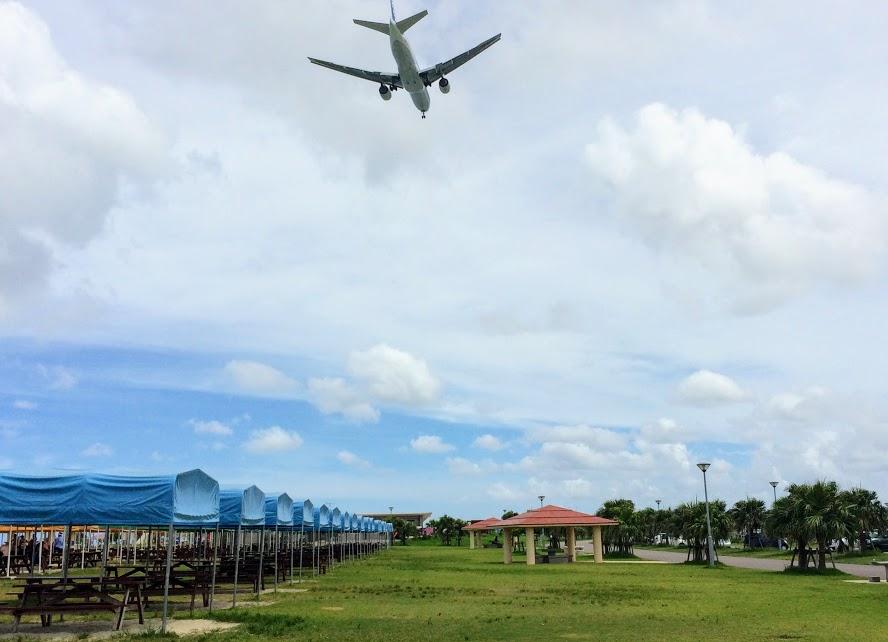 美らサンビーチ上空を飛ぶ着陸体制の飛行機
